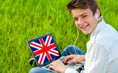 Portrait of attractive teen boy learning english on laptop outdoors.